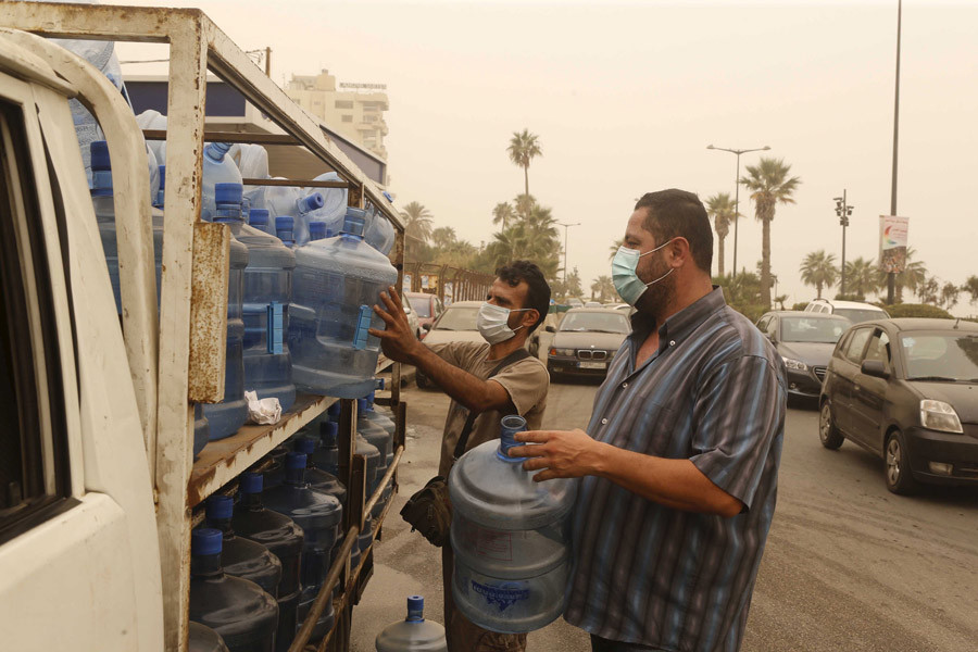Workers carrying gallons of water wear face masks during a sandstorm in Beirut