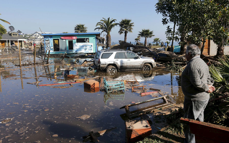 A man looks at a car next to a shop destroyed by waves after an earthquake hit areas of central Chile, in Concon city