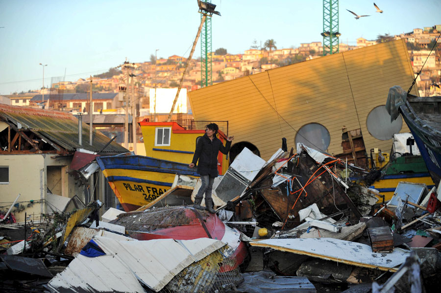 A woman recovers items from her destroyed house after an earthquake hit areas of central Chile, in Coquimbo city