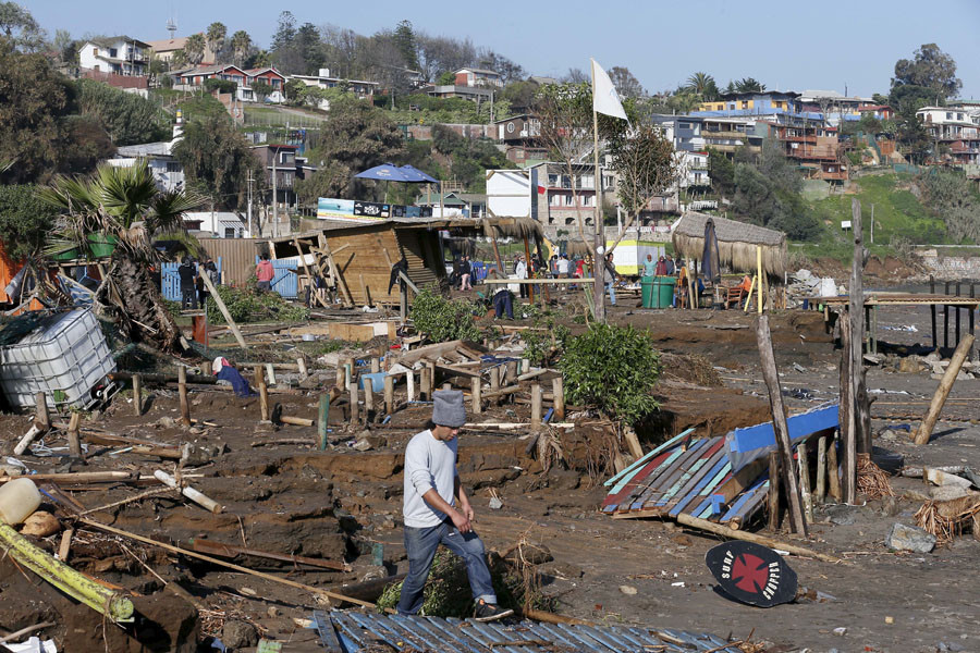 A man walks next to destroyed houses and shops after an earthquake hit areas of central Chile, in Concon city