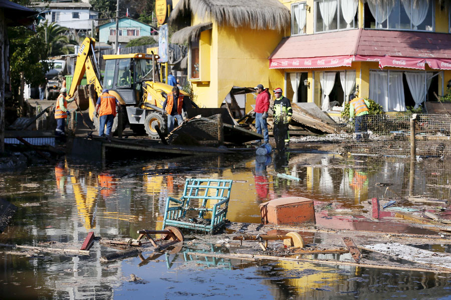 People work on removing the debris of houses and shops destroyed by waves after an earthquake hit areas of central Chile, in Concon city