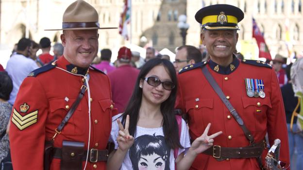 OTTAWA, CANADA - JULY 1: Two Royal Canadian Mounted Police officers pose for pictures as thousands gather on Parliament Hill to celebrate Canada Day on July 1, 2012 in Ottawa, Canada. Ottawa, the captial of Canada, is home to the largest celebration of Canada Day in the country. (Photo by George Rose/Getty Images)