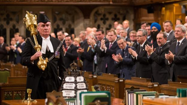 OTTAWA, CANADA - OCTOBER 23:  In this handout photo provided by the PMO, Prime Minister Stephen Harper (R) and all Members of Parliament applaud Kevin Vickers, Sergeant-at-Arms, during the reopening of Parliament on October 23, 2014 in Ottawa, Canada. The gunman, identified as Michael Zehaf-Bibeau, was shot and killed by Kevin Vickers while still inside the Parliament building.  (Photo by Jason Ransom/PMO via Getty Images)