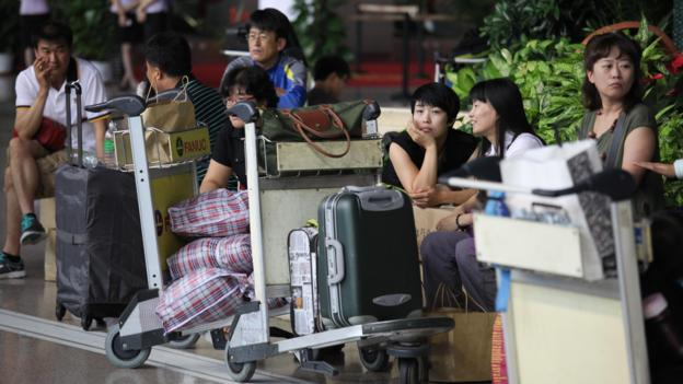 SHANGHAI, CHINA - AUGUST 08:  (CHINA OUT) Passengers wait for their flights at an airport on August 8, 2012 in Shanghai, China. Typhoon Haikui, the 11th typhoon to hit China this year, landed in central Zhejiang's Hepu Town early Wednesday.  (Photo by ChinaFotoPress/Getty Images)