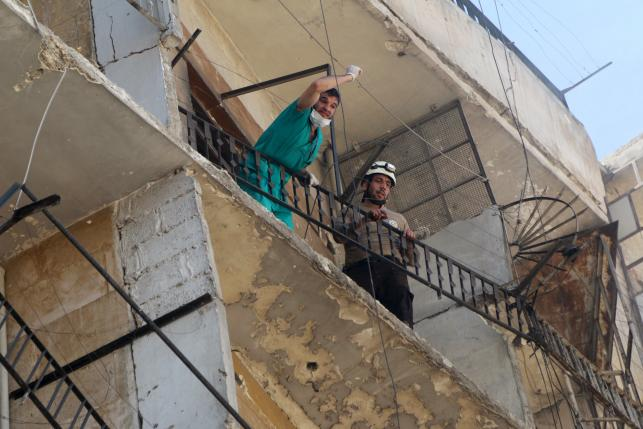 Civil defence members gesture on a damaged balcony after an airstrike on the rebel-held Tariq al-Bab neighbourhood of Aleppo, Syria April 23, 2016. REUTERS/Abdalrhman Ismail