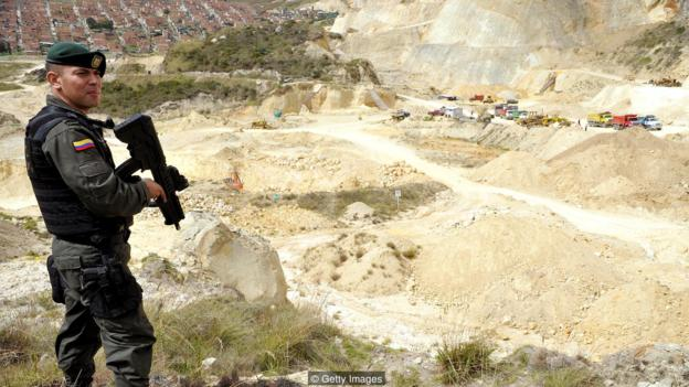 A police officer stands guard in a gravel, sand and stone quarry in the municipality of Soacha, outskirts of Bogota, on June 27, 2013. In a joint Police-Justice Department-Ministry of Environment of Bogota raid against illegal mining, ten people were arrested and machinery confiscated. AFP PHOTO/Guillermo LEGARIA        (Photo credit should read GUILLERMO LEGARIA/AFP/Getty Images)