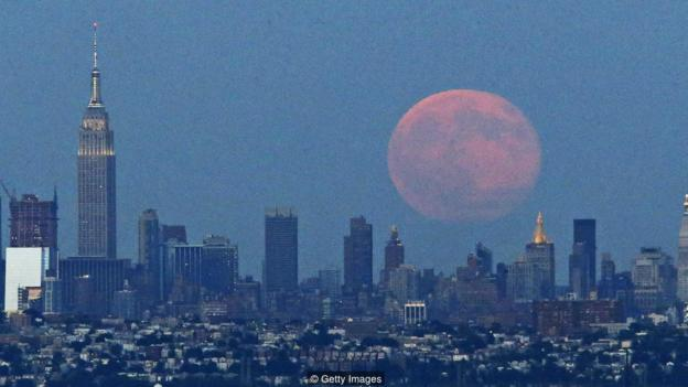 A Blue Moon rises over the skyline of New York City from West Orange in New Jersey on July 31, 2015. PHOTO/KENA BETANCUR        (Photo credit should read KENA BETANCUR/AFP/Getty Images)
