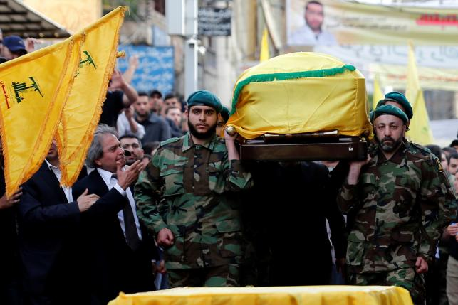 Hezbollah members carry the coffin of top Hezbollah commander Mustafa Badreddine, who was killed in an attack in Syria, as his brother mourns his death during his funeral in Beirut's southern suburbs, Lebanon, May 13, 2016. REUTERS/Jamal Saidi